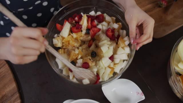 vídeos de stock, filmes e b-roll de crianças fazendo salada de frutas em casa. - fruit salad