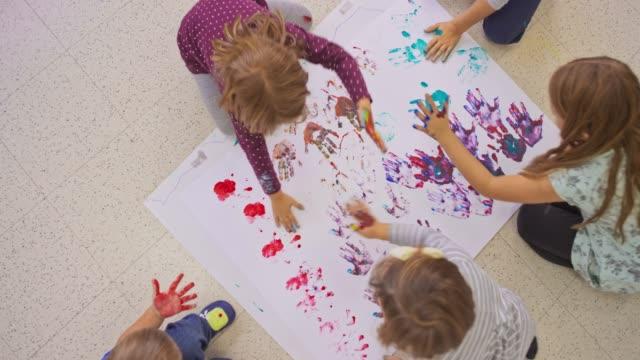 Miúdos que fazem handprints em um livro branco no assoalho - vídeo