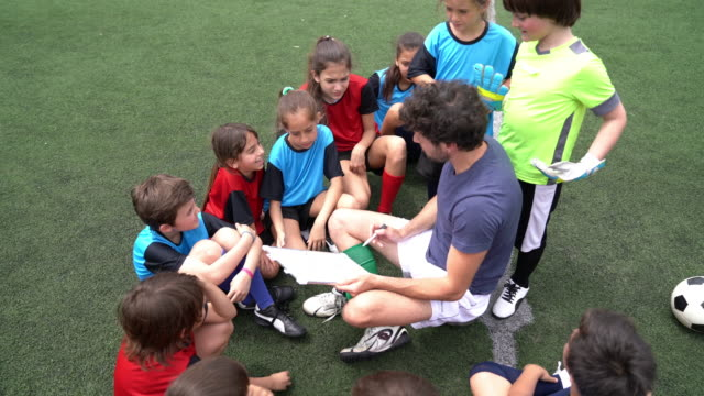 Kids of a soccer team listening to their coach, sitting together on a soccer field video