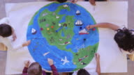 istock Kids painting mural of the world 1155101014