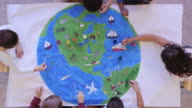 istock Kids painting mural of the world 1155101028