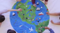 istock Kids painting mural of the world 1155101047