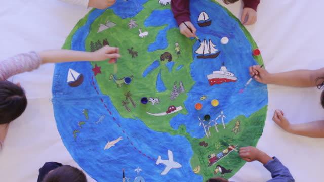 barn målar väggmålning av världen - väggmålning bildbanksvideor och videomaterial från bakom kulisserna