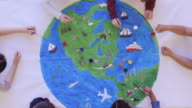 istock Kids painting mural of the world 1155101655