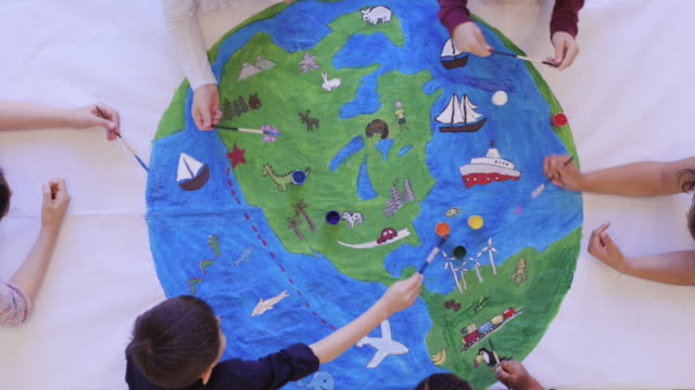 Kids painting mural of the world
