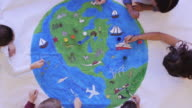 istock Kids painting mural of the world 1164033317