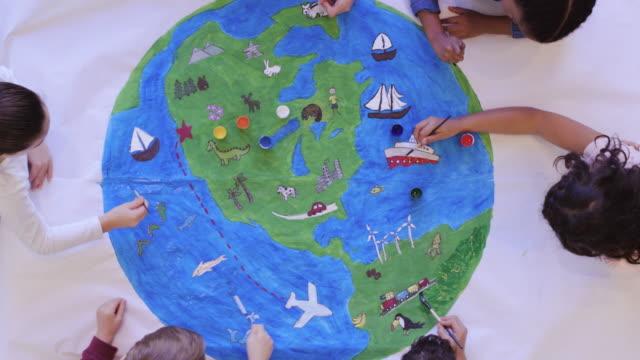 vídeos de stock e filmes b-roll de kids painting mural of the world - green world