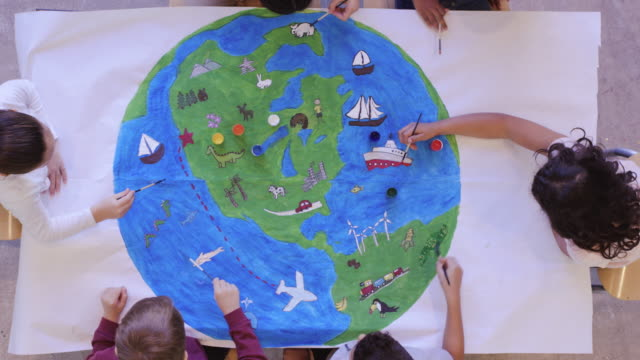 Kids painting mural of the world Aerial overhead view of multi-ethnic group of elementary age children painting the globe. The kids are seated around a large table. They have painted the world and various means of transportation. Global travel concept. mural stock videos & royalty-free footage