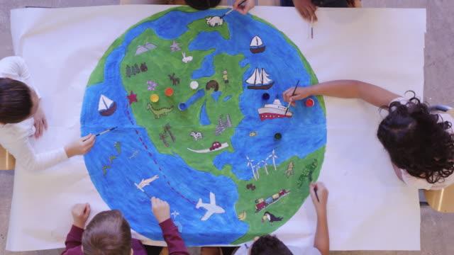 barnen målar väggmålning av världen - väggmålning bildbanksvideor och videomaterial från bakom kulisserna