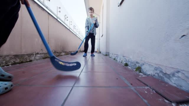 vídeos y material grabado en eventos de stock de niños jugando hockey ad hoc en el balcón - stay home