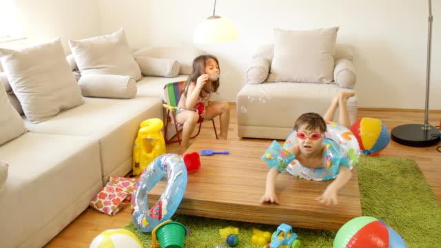 vídeos de stock, filmes e b-roll de crianças brincando em casa, fantasia com cerca de verão praia e o mar. - inflável