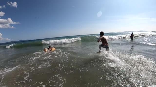 vídeos de stock, filmes e b-roll de miúdos que jogam em ondas do mar no movimento lento - férias na praia