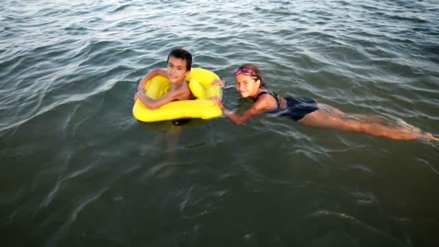 barn som leker i havet - inflatable ring bildbanksvideor och videomaterial från bakom kulisserna