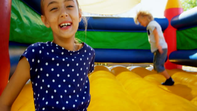 vídeos de stock e filmes b-roll de kids playing on the bouncing castle 4k - castle