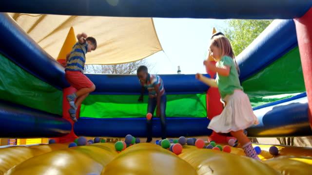 vídeos de stock, filmes e b-roll de crianças brincando no castelo saltitante 4k - castelo