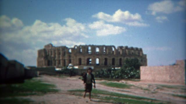 tunisi, tunisia 1972: bambini giocare come il colosseo romano sfondo con cielo blu. - colosseo 1900 video stock e b–roll