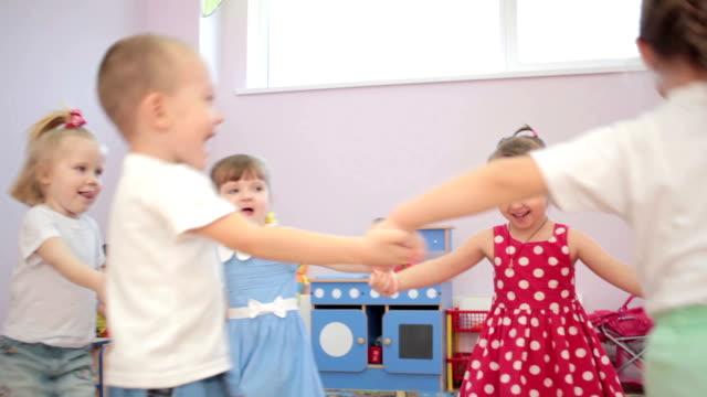 Kids playing running around dancing in kindergarten and laughter video