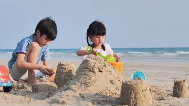 ビーチでサンドボックスをプレイする子供たち。幸せな家族は、ビーチで夏の休暇をお楽しみください。夫婦関係。休暇-istock - 兄弟姉妹点の映像素材/bロール