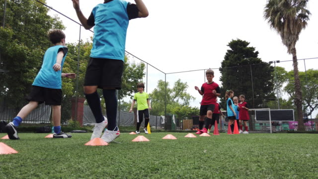 Kids playing soccer - Boys and Girls on a football court in training - video