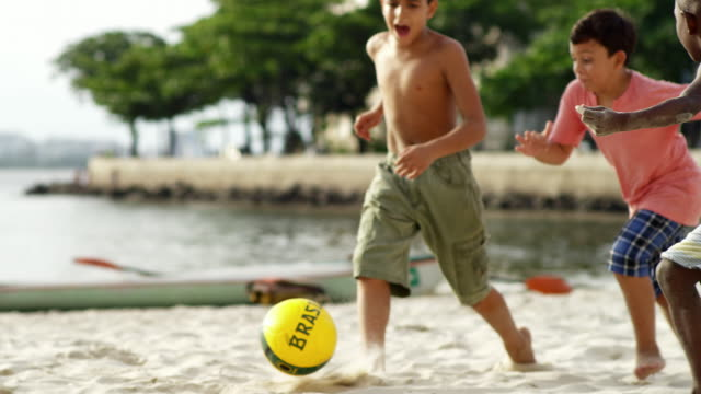 Kids playing soccer on a beach in Brazil Kids playing soccer on a beach in Brazil brazil stock videos & royalty-free footage
