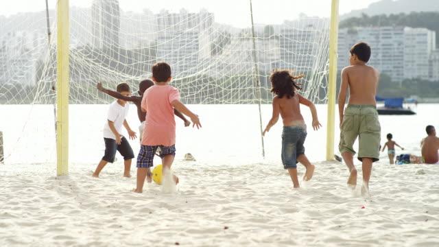 Crianças jogando futebol na praia no Brasil - vídeo