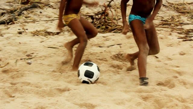 vídeos de stock e filmes b-roll de crianças jogando futebol na praia - ronaldo