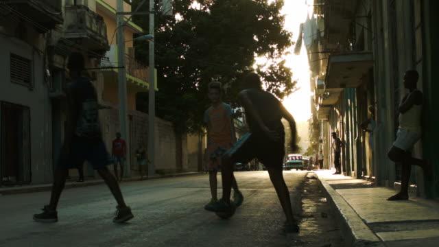 barn spelar fotboll på trottoaren i gamla havanna - walking home sunset street bildbanksvideor och videomaterial från bakom kulisserna