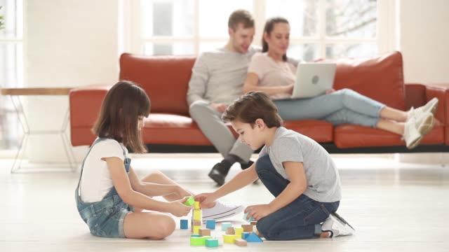 kinder spielen mit spielzeugblöcken auf warmem boden - vollzeit elternteil stock-videos und b-roll-filmmaterial