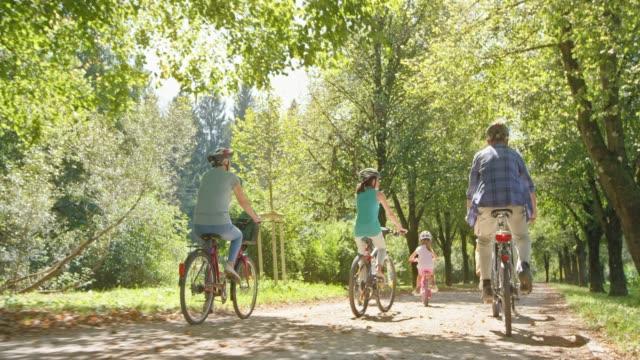 pov kinder fahrradfahren im park mit eltern, geschwistern und großeltern an einem sonnigen tag - 2 3 jahre stock-videos und b-roll-filmmaterial