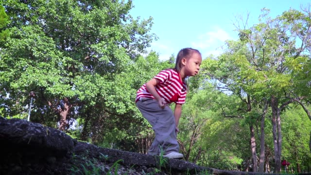 kids run and jump over a weeds during blue sky in summer. Jump cross the little stream.