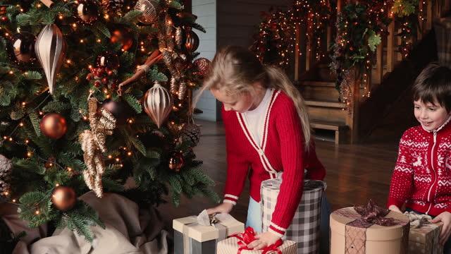 stockvideo's en b-roll-footage met de jonge geitjes lopen onderaan de treden om dozen met giften te openen - christmas tree