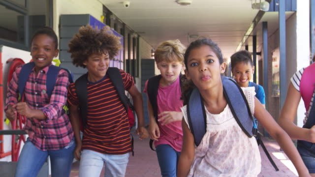 Kids running in school hallway, front view, close up video