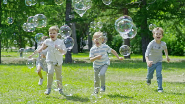 Kids Running on Green Lawn and Popping Soap Bubbles video