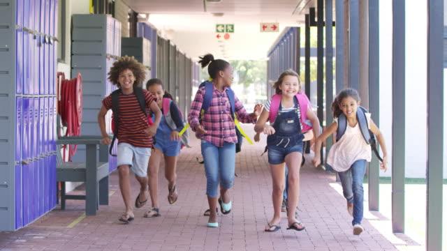 Niños corriendo a cámara en el pasillo de la escuela, vista frontal - vídeo