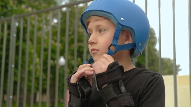 stockvideo's en b-roll-footage met kids veiligheidsuitrusting boy put helm rollerblade - schooljongen