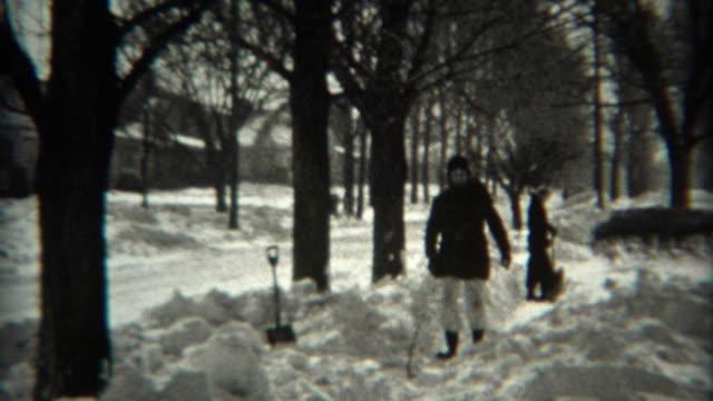 1936: Kids shoveling sidewalk snow after blizzard storm blankets home.