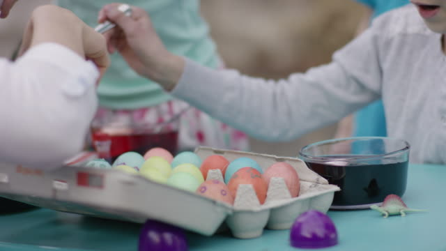 Kids sitting at a table decorating Easter eggs video