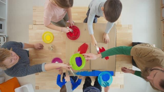 vidéos et rushes de ld kids assis à la table et la peinture d'une boîte en carton - art et artisanat