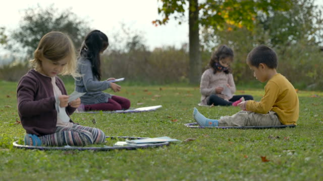 Kids sitting in hula hoops on the ground in a modified outdoor classroom