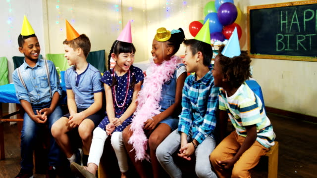 Kids smiling while sitting together during birthday party 4k video