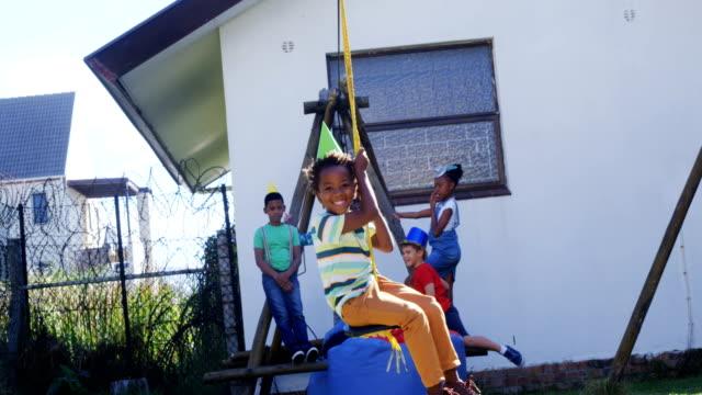 Kids swinging in a rope swing 4k video
