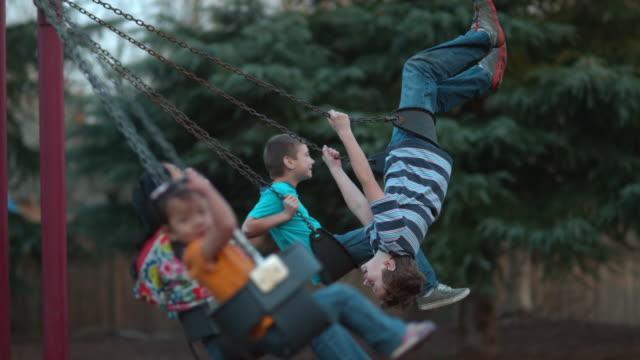 kids swinging in slow motion - oscillare video stock e b–roll