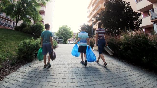 kids taking out the segregated garbage - odzyskiwanie i przetwarzanie surowców wtórnych filmów i materiałów b-roll