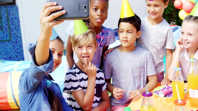 Kids taking selfies with mobile phone in the backyard of house 4k video