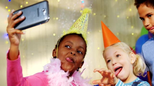 barnen pratar selfie under födelsedag part 4k - birthday celebration looking at phone children bildbanksvideor och videomaterial från bakom kulisserna