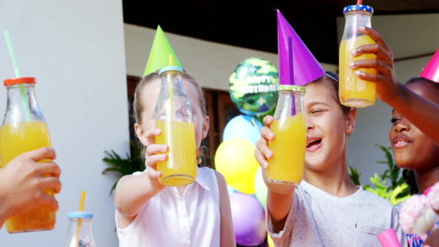 Kids toasting the bottles of juice in the backyard of house 4k video