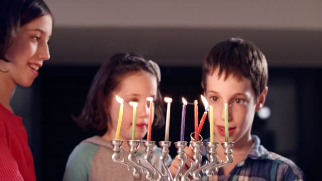 Kids watching a hanukka menora with candles video