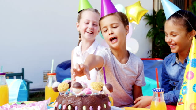 Kids with birthday cake at the backyard of house 4k video
