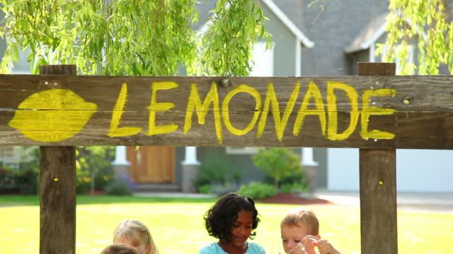 vídeos de stock e filmes b-roll de crianças com barraca de venda de limonada - limonada tradicional