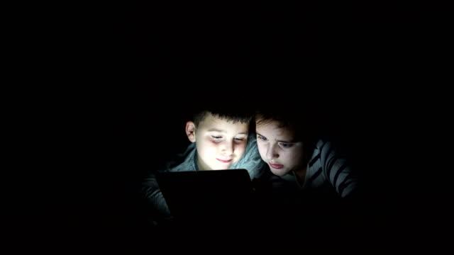 Niños con tablet PC en una habitación oscura - vídeo